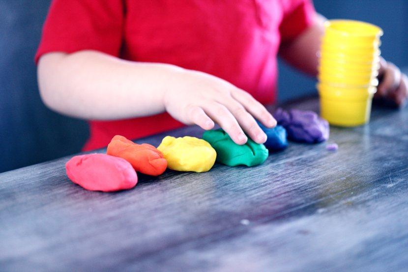 Omogenitorialità: un bambino gioca con il pongo dei colori dell'arcobaleno